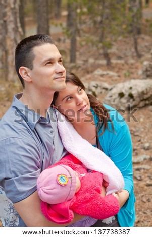Parents holding baby daughter while looking up - stock photo