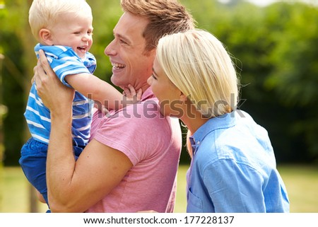 Parents Hugging Young Son In Garden - stock photo