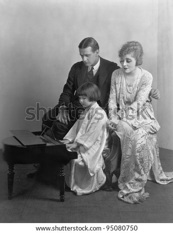 Parents listening to daughter play miniature piano - stock photo
