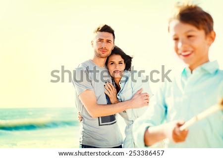 parents look her son while she enjoys playing on the beach sea - stock photo