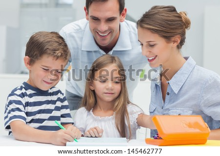 Parents looking at their children drawing in the kitchen - stock photo