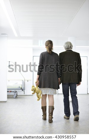 Parents Man Woman with teddy bear in the hallway of a hospital standing - stock photo