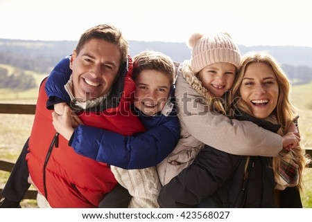 Parents piggy back kids in the countryside looking to camera - stock photo