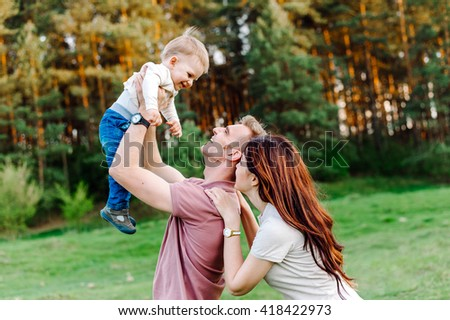 Parents play with their child. Father holding a child in his arms. They are happy. Happy family walking outdoor. - stock photo