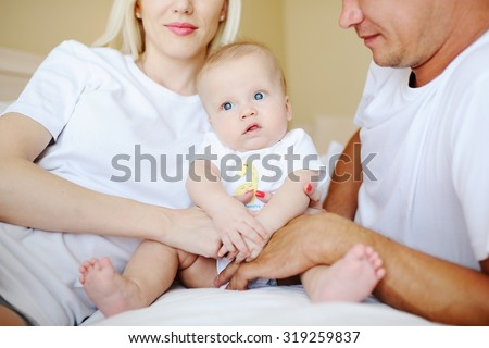 Parents playing with baby in bed - stock photo