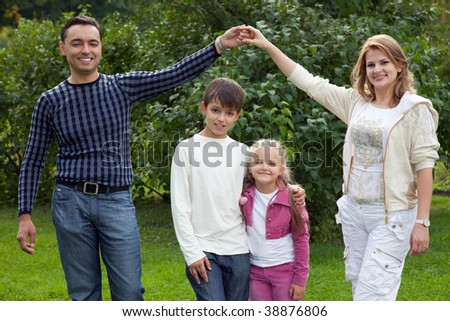 parents playing with children in park, making house - stock photo