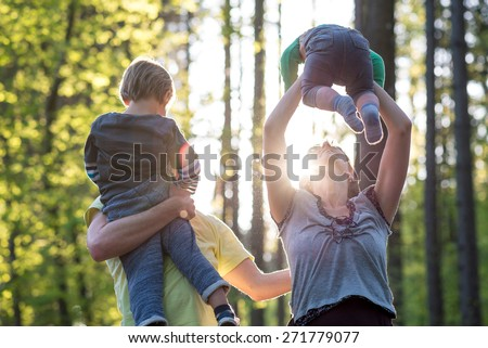 Parents playing with their two young children outdoors in a green spring forest backlit by a glowing sun as they enjoy the tranquility of nature. - stock photo
