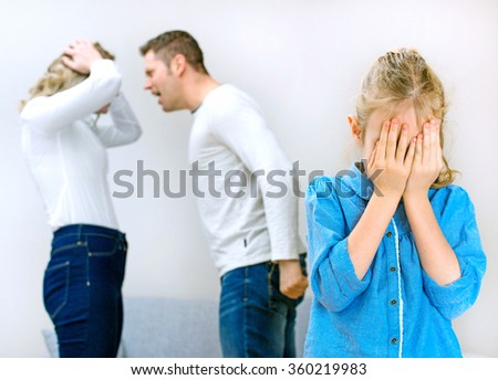 Parents quarreling at home, child is crying. - stock photo