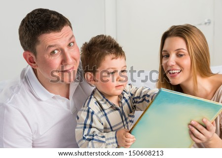 Parents Sitting With Child Reading Story Indoors - stock photo