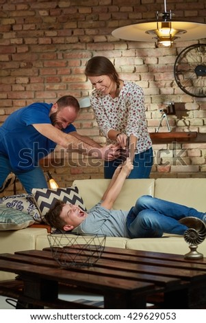 Parents taking away tablet from son, boy screaming. - stock photo