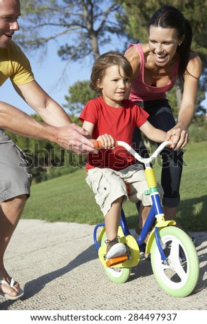 Parents Teaching Son To Ride Bike In Park - stock photo