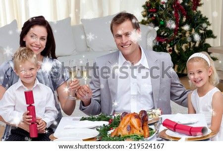 Parents toasting with wine in Christmas dinner against snow falling - stock photo