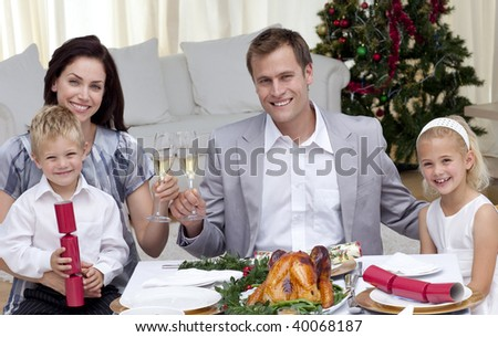 Parents toasting with wine in Christmas dinner at home - stock photo