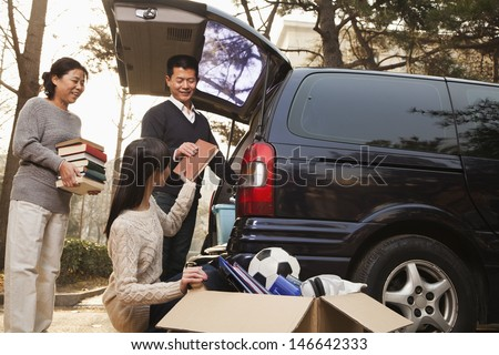 Parents unpacking car for a move to college, Beijing - stock photo
