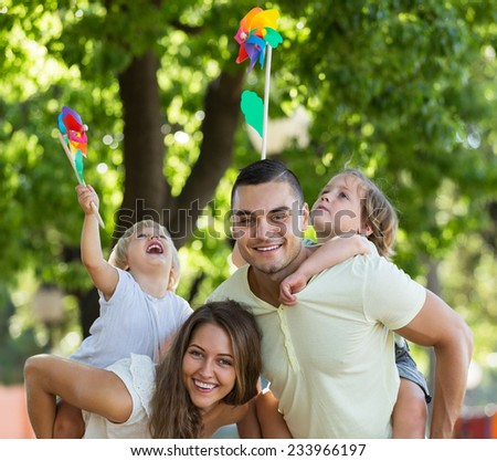 Parents walking with children on bright vacation day at park  - stock photo