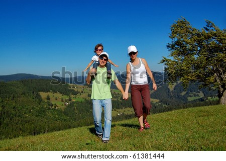 Parents with a child having a walk outdoors - stock photo