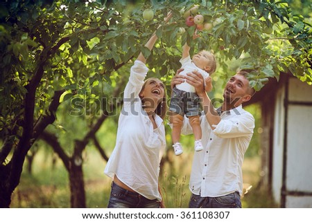 Parents with baby enjoying picnic on a farm with apple and cherry trees.  - stock photo