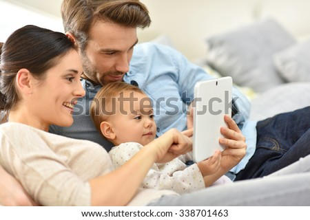 Parents with baby girl in sofa using digital tablet - stock photo