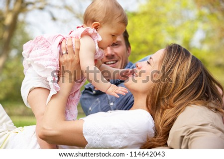 Parents With Baby Girl Sitting In Field Of Summer Flowers - stock photo
