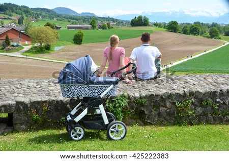 Parents with baby stroller enjoing Alpine panorama. Switzerland - stock photo