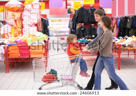 Parents with child in cart in supermarket - stock photo