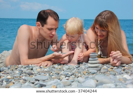 Parents with child on sea coast and  pyramid of stones - stock photo
