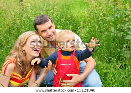 Parents with child sit in grass and look upwards - stock photo