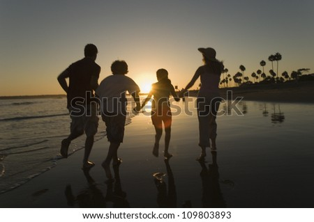 Parents with children holding hands and running on beach - stock photo