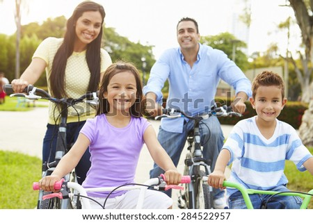 Parents With Children Riding Bikes In Park - stock photo