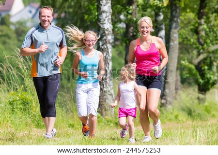 Parents with children sport running together through forest  - stock photo