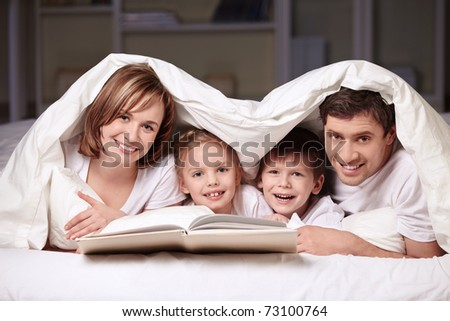 Parents with children under the blanket with a book - stock photo