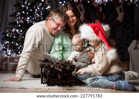 Parents with children write letters to Santa Claus sitting under the Christmas tree by the fireplace - stock photo