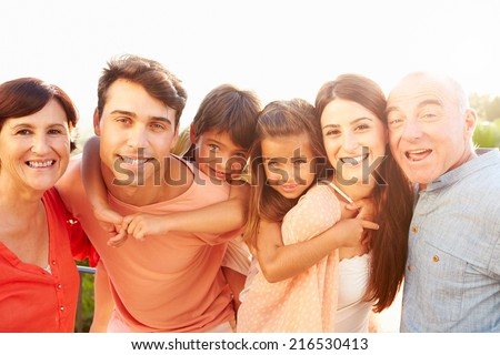 Parents With Grandparents Giving Children Piggyback Ride - stock photo