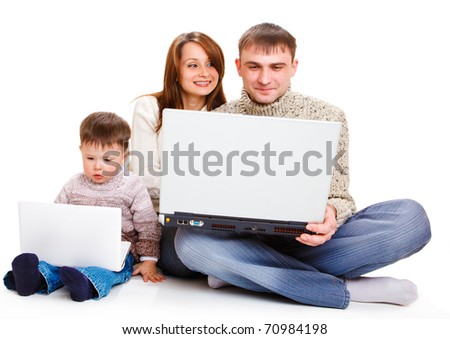 Parents with large laptop and toddler boy with a small one - stock photo