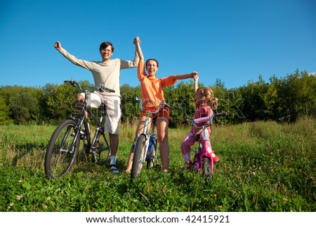Parents with the daughter on bicycles in park a sunny day. Have joyfully thrown up hands. - stock photo