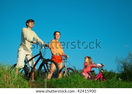 Parents with the daughter on bicycles, in the summer evening. - stock photo