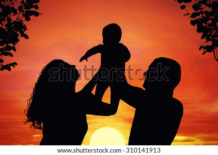 Parents with their little child at sunset, raising baby up in the air. Silhouette of a happy family of three people, mother, father and baby - stock photo