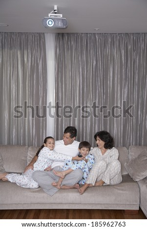 Parents with two children watching TV - stock photo