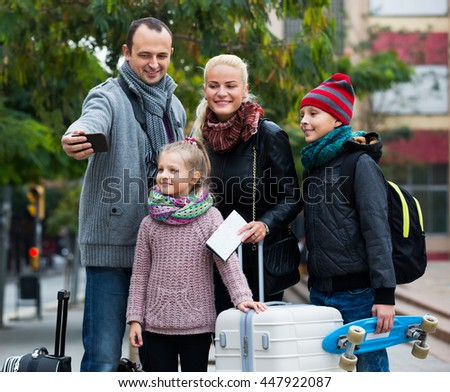 Parents with two kids and baggage taking selfie on a smartphone  - stock photo