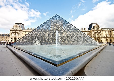 PARIS - APRIL 16. Glass pyramid and the Louvre museum on April, 16, 2012. The Louvre is the biggest museum in Paris with nearly 35,000 objects from prehistory to the 19th century are exhibited there. - stock photo