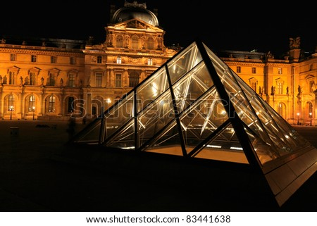 PARIS - APRIL 6: Night view of The Louvre Palace and the Pyramid on April 06, 2011 in Paris. Louvre is most visited museum in the world with 8.5 million visitors per year. - stock photo