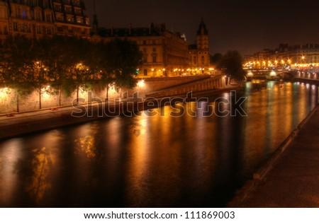 Paris at night: river Seine and illuminated riverbank at Ile de la Cite. - stock photo
