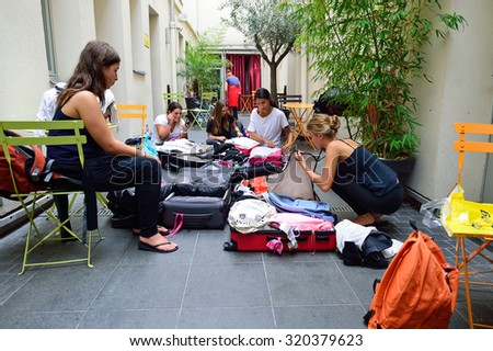 PARIS - AUGUST 08, 2015: girls collect luggage in the hostel. Hostels provide budget-oriented, sociable accommodation where guests can rent a bed in a dormitory and share a bathroom. - stock photo