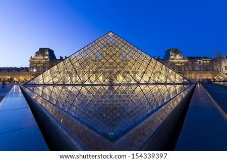 PARIS - AUGUST 11: Louvre pyramid shining at dusk during the Summer Exhibition on August 11,2013 in Paris.Louvre is the biggest Museum in Paris displayed over 60,000 square meters of exhibition space. - stock photo