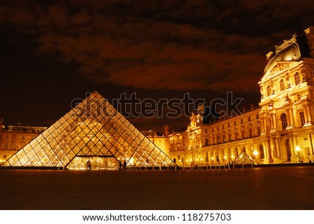 PARIS - AUGUST 18 : Pyramid and Pavillon Rishelieu in Louvre, August 18, 2007, Paris. Louvre is the biggest Museum in Paris displayed over 60,000 square meters of exhibition space. - stock photo