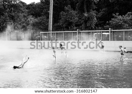 PARIS - AUGUST 29: Unknown children playing in the steaming water in Jardin d'Acclimatation, in front of Foundation Louis Vuitton in Paris, France on 29 August 2015 - stock photo