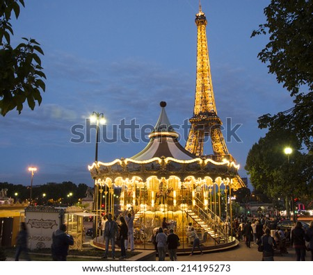 PARIS - August 21: Vintage merry-go-round at night with the illuminated Eiffel Tower in the background on August 21, 2014 in Paris. - stock photo