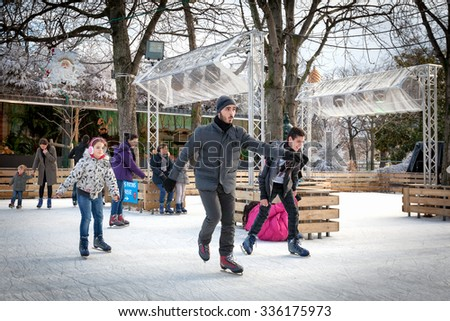 PARIS-Dec 25, 2013: Christmas ice skating at Santa's Village and the Christmas Market on the Avenue des Champs-Elysees, a holiday tradition in Paris that attracts both locals and tourists. - stock photo