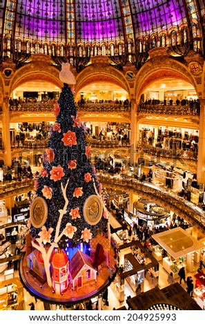 PARIS-DEC 24,2013:Christmas tree at the 10-story Galeries Lafayette department store, shown here on Christmas Eve. At 20 meters, the famous tree is the world's tallest indoor Christmas tree display. - stock photo