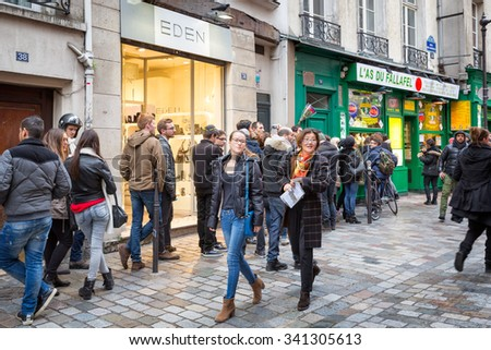 PARIS - Dec 23, 2013: Historic Jewish quarter. Rue des Rosiers, a picturesque street in an area of small shops visited by locals and tourists. People line up at a popular fallafel restaurant. - stock photo